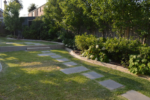 Side view taken of backyard with lots of plants and paved paths.
